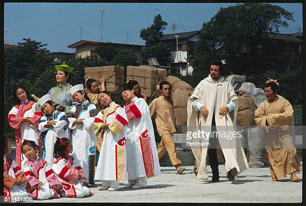 Desi Arnaz Jr emoting on the set of Marco Polo is surrounded by children The film is being shot at Toho outdoor studio near Tokyo
