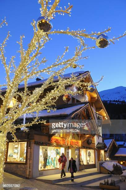 Design Christmas tree and Sport Boutique sportswear for winter sport shop at night Meribel ski resort Trois Vallees skiing area Tarentaise valley...