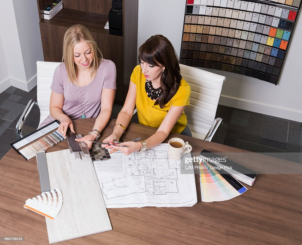 design consultant and interior designer selecting paint and tile samples in a tile store stock