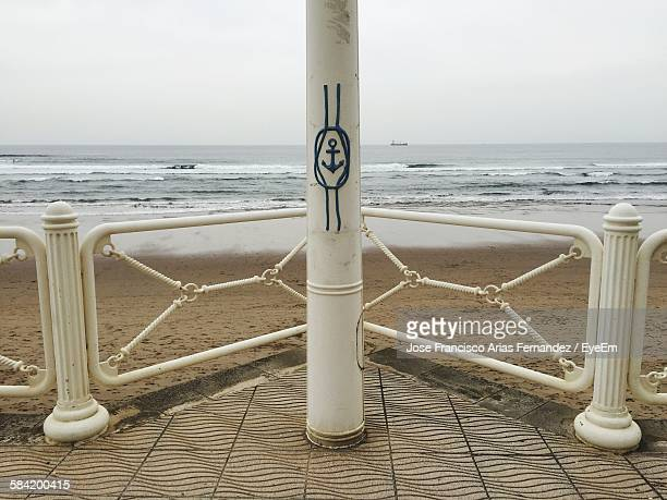 Design Of Anchor On Metallic Pole At Beach Against Sky
