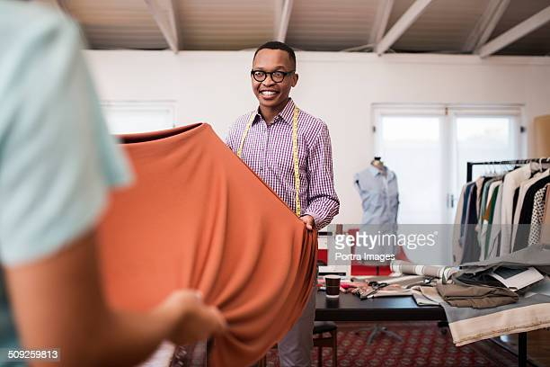 design professional holding fabric with colleague - fashion designer stock pictures, royalty-free photos & images