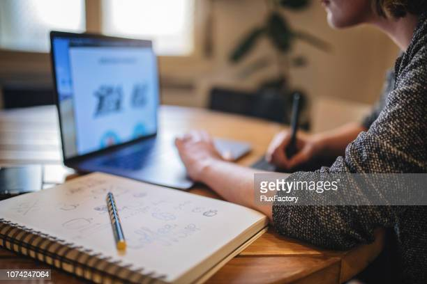 design student doing homework at home - logo design stock photos and pictures