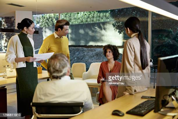 design team discussing project plans in modern office - creative director stock pictures, royalty-free photos & images