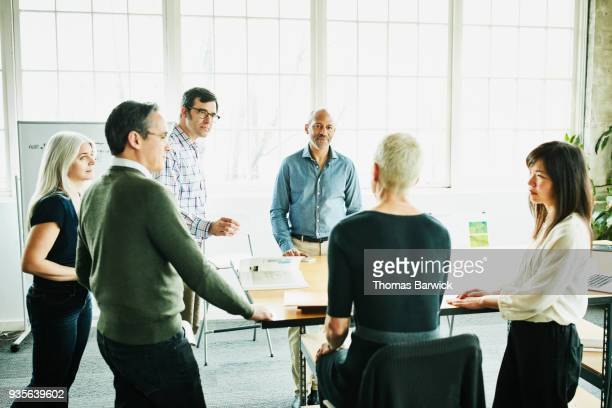 Design team listening to female architect lead planning meeting in office conference room