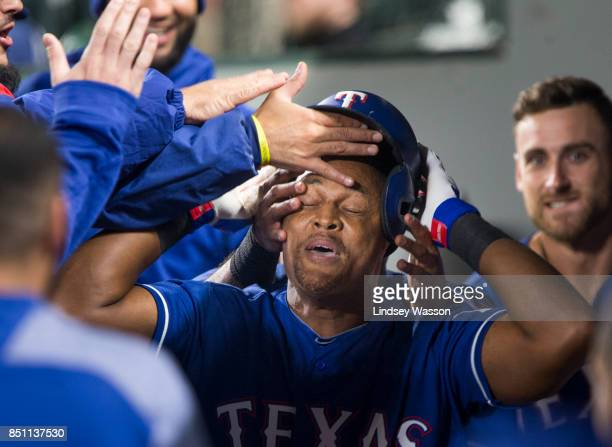 Designated hitter Adrian Beltre of the Texas Rangers reacts as he's mobbed in the dugout and has his batting helmet grabbed by a teammate after...