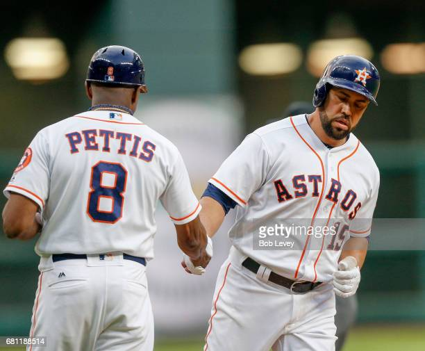 Designated hitter Carlos Beltran of the Houston Astros receives congratulations from third base coach Gary Pettis after a first inning home run...