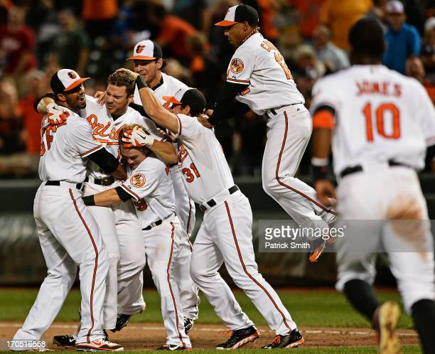 Designated hitter Chris Davis of the Baltimore Orioles is mobbed by teammates after hitting the gamewinning RBI against the Boston Red Sox in the...