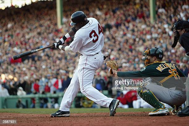 Designated hitter David Ortiz of the Boston Red Sox hits a tworun double in the bottom of the eighth inning to drive in the winning runs in game four...