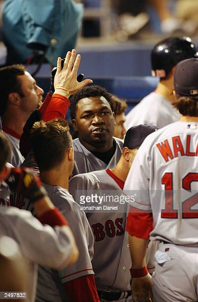 Designated hitter David Ortiz of the Boston Red Sox is congratulated by teammates in the dugout after hitting the game winning home run in the tenth...