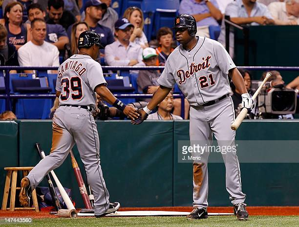 Designated hitter Delmon Young of the Detroit Tigers congratulates Ramon Santiago after he scored against the Tampa Bay Rays during the game at...