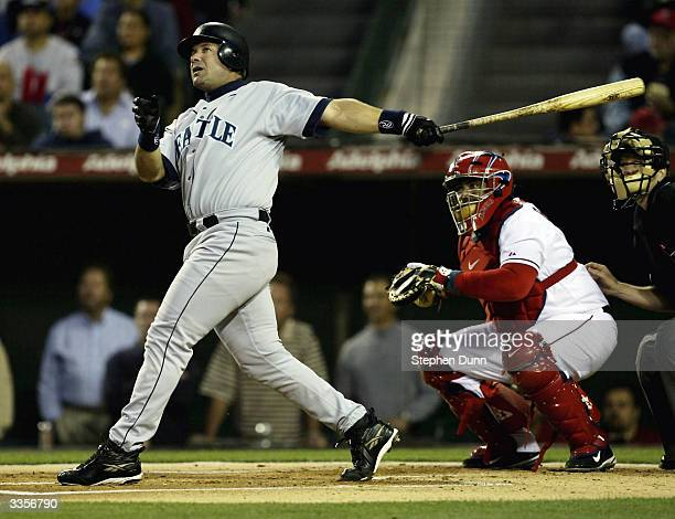 Designated hitter Edgar Martinez of the Seattle Mariners hits a two run home run in the first inning as catcher Bengie Molina of the Anaheim Angels...