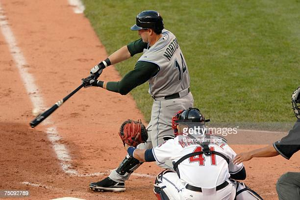 Designated hitter Greg Norton of the Tampa Bay Devil Rays grounds out as catcher Victor Martinez of the Cleveland Indians looks on during their game...