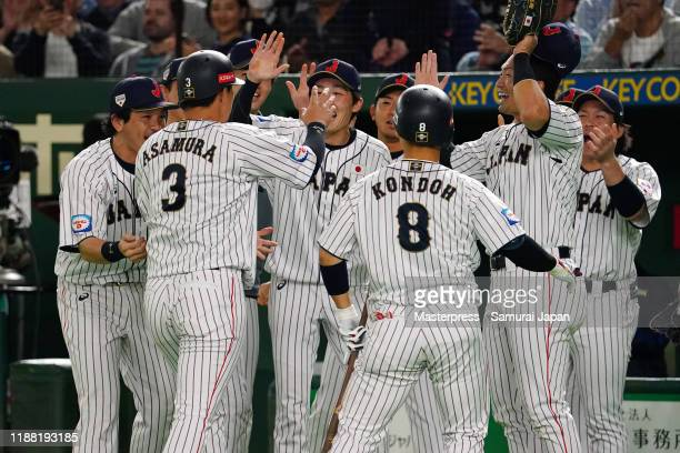 Designated hitter Hideto Asamura of Japan is congratulated by his team mates after hitting a RBI single after the bottom of 7th inning during the...