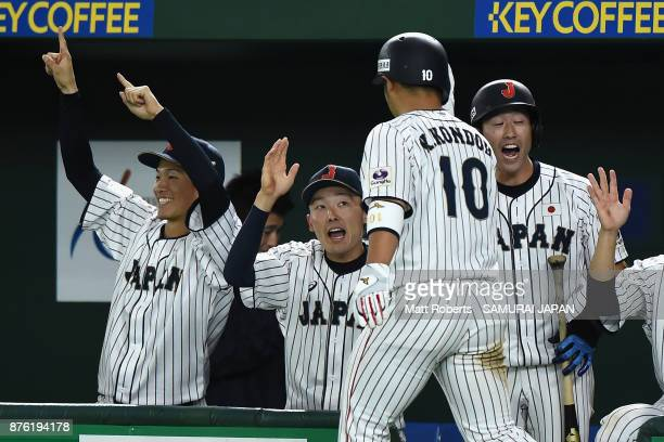 Designated hitter Kensuke Kondo of Japan high fives with team mates after scoring a run by the two run single of Infielder Hotaka Yamakawa in the...