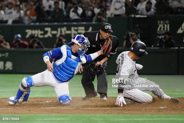 Designated hitter Kensuke Kondo of Japan is tagged out by Catcher Han Seungtaek of South Korea in the bottom of fifth inning during the Eneos Asia...