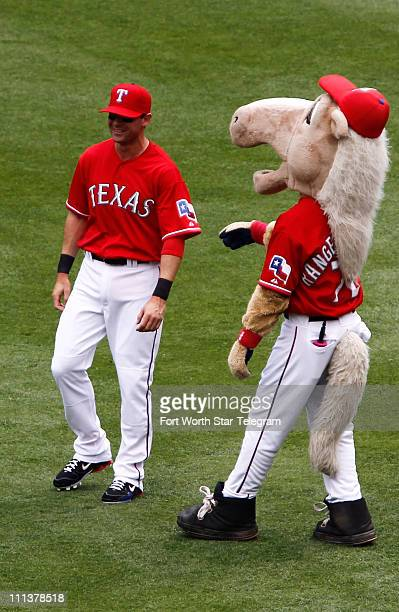 Designated hitter Michael Young jokes with the team mascot before the 2011 home opener at the Rangers Ballpark in Arlington Texas on Friday April...