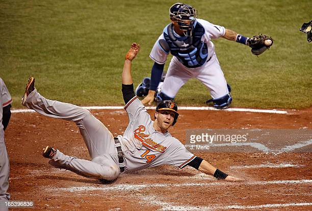 Designated hitter Nolan Reimold of the Baltimore Orioles scores a run in the seventh inning as catcher Jose Lobaton of the Tampa Bay Rays missed the...