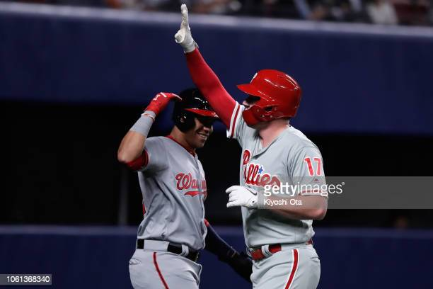 Designated hitter Rhys Hoskins of the Philadelphia Phillies celebrates hitting a two-run home run to make it 2-0 with Outfielder Juan Soto of the...