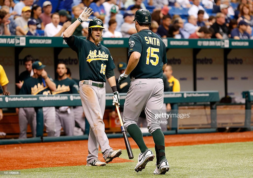 Designated hitter Seth Smith #15 of the Oakland Athletics is congratulated by Josh Reddick #16 after his home run against the Tampa Bay Rays during the game at Tropicana Field on August 25, 2012 in St. Petersburg, Florida.