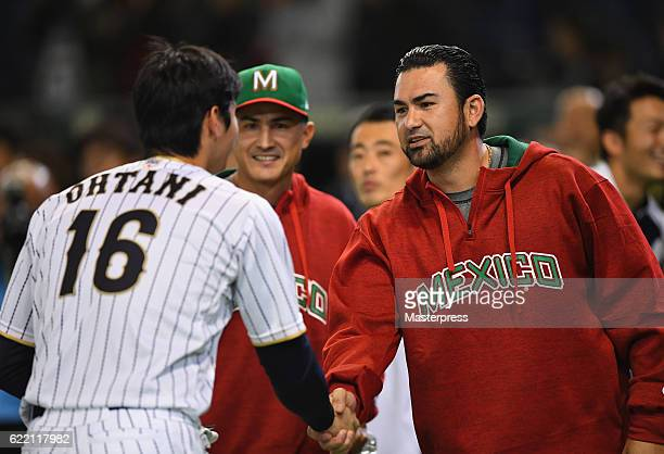 Designated hitter Shohei Ohtani of Japan and Infielder Adrian Gonzalez of Mexico shake hands during a practice session prior to the international...
