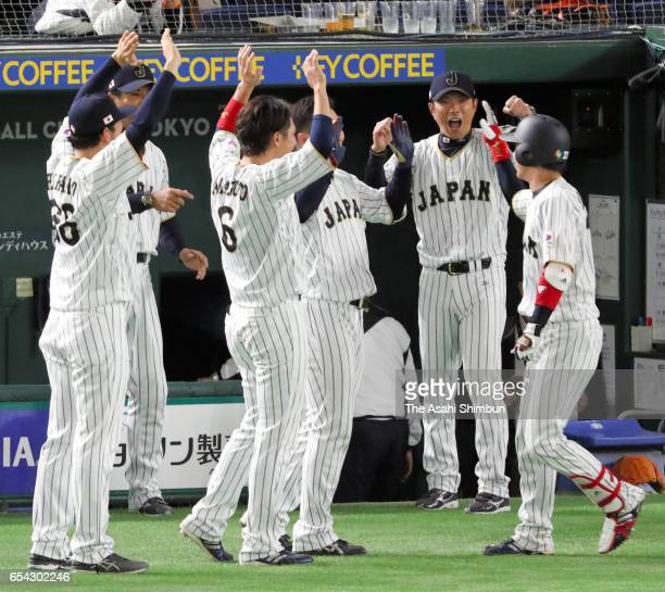 Designated hitter Tetsuto Yamada of Japan is congratulated by his team mates after hitting a two run homer in the bottom of the eighth inning during...