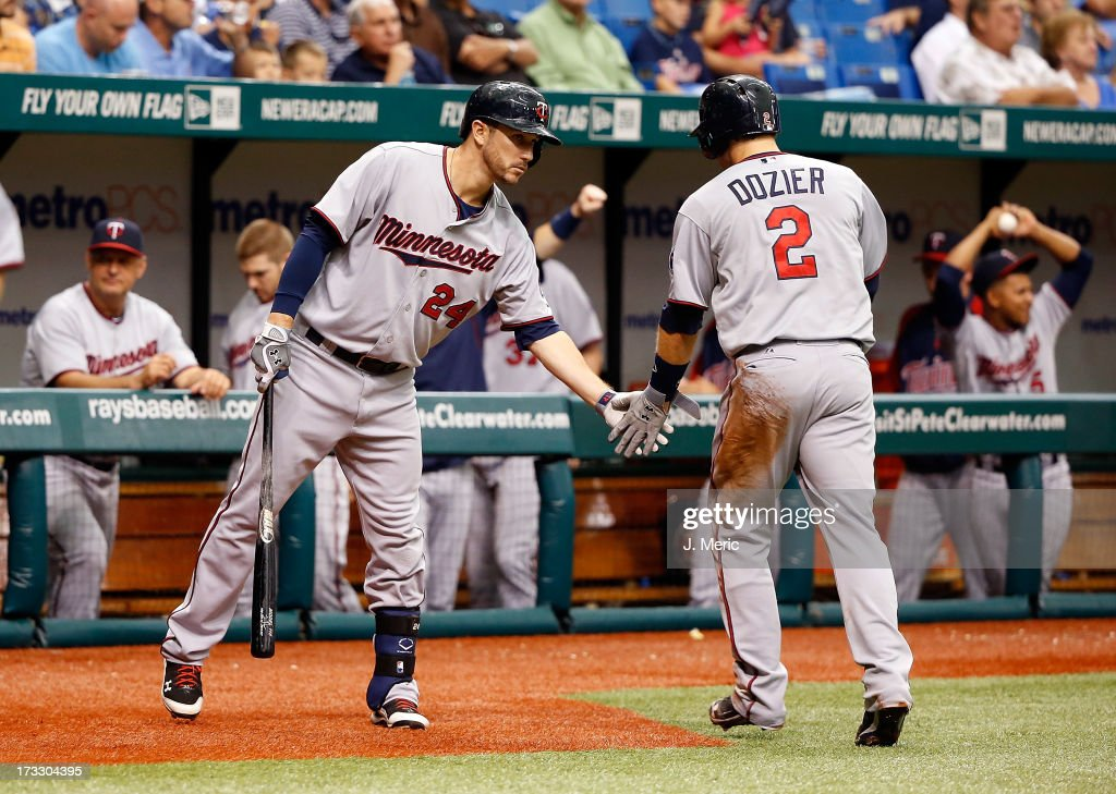 Designated hitter Trevor Plouffe #24 of the Minnesota Twins congratulates Brian Dozier #2 after scoring a sixth inning run against the Tampa Bay Rays during the game at Tropicana Field on July 11, 2013 in St. Petersburg, Florida.