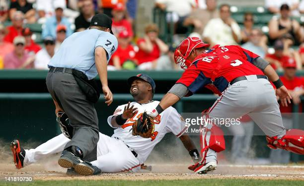 Designated hitter Wilson Betemit of the Baltimore Orioles is tagged out at home by catcher Wilson Ramos of the Washington Nationals during a...