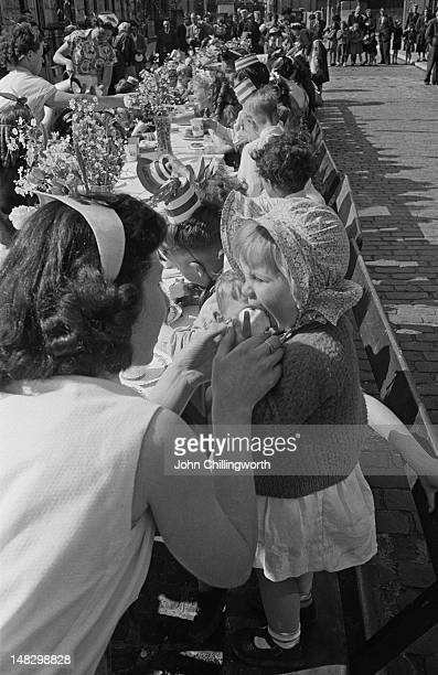 A designated waitress feeds a child at a street party to celebrate the coronation of Queen Elizabeth II held in Morpeth Street in London's East End...