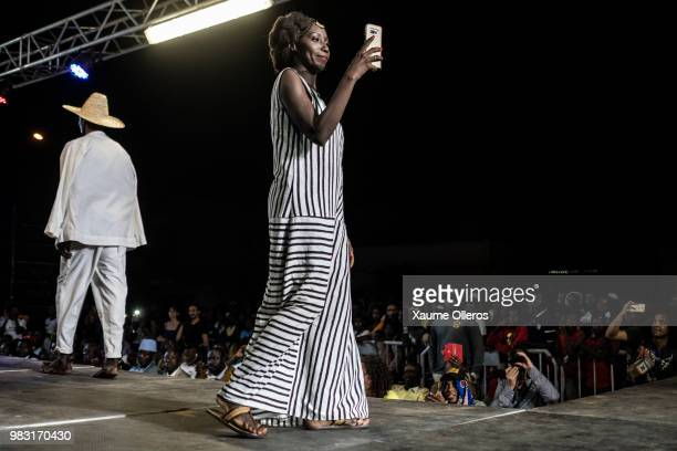 Designer Adama Paris takes pictures with her phone after her show during last day of the Dakar Fashion Week at the working class suburb of Keur...