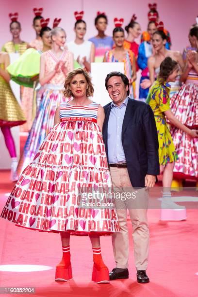 Designer Agatha Ruiz De La Prada and Hola magazine director Eduardo Sanchez Perez walk the runway after her fashion show during the Mercedes Benz...
