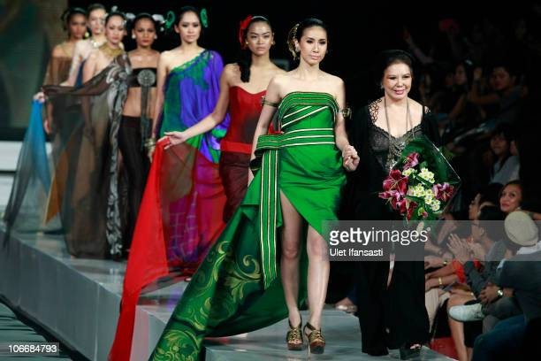 Designer Agnes Budhisurya walks the catwalk with models following her collection show as part of APPMI show on the fourth day of Jakarta Fashion Week...