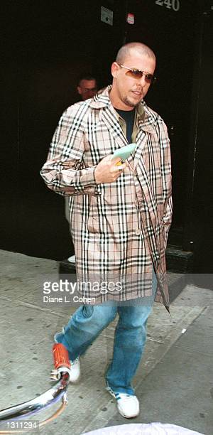 """Designer Alexander McQueen wears a Burbury plaid rain coat May 20, 2001 as he walks to the """"The Genesis of Fashion"""" discussion at Club Float in New..."""
