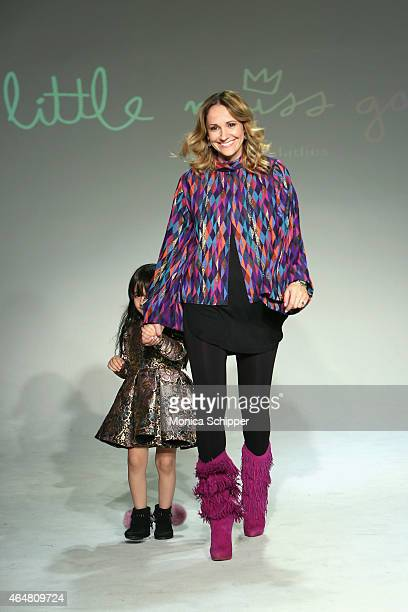 Designer Alia Charvel walks the runway with a model at the Little Miss Galia show during petitePARADE / Kids Fashion Week at Bathhouse Studios on...
