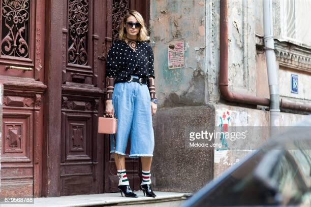 ANOUKI designer Ana Areshidze wears Rag Bone culotte jeans Gucci socks Balenciaga shoes and a DSquared2 top under a Zara top at MercedesBenz Fashion...