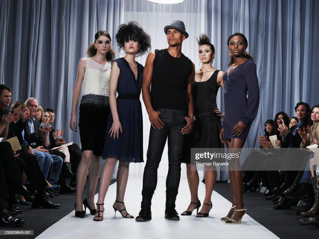 Designer and female models standing on catwalk : Stock Photo