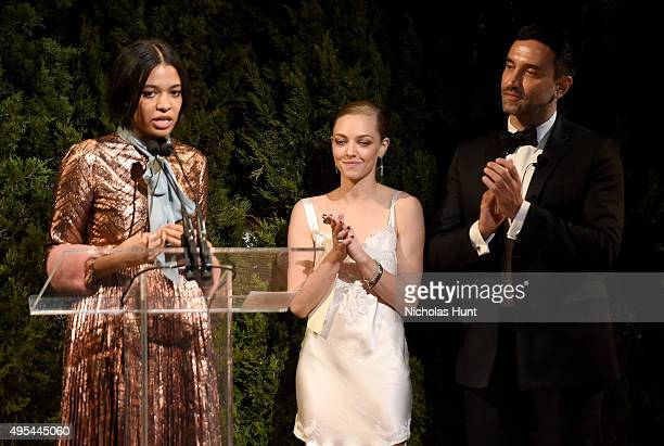 Designer and winner Aurora James accepts an award onstage with Actress Amanda Seyfried and designer and keynote speaker Riccardo Tisci at the 12th...