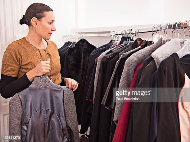 Designer arranges garments on rack