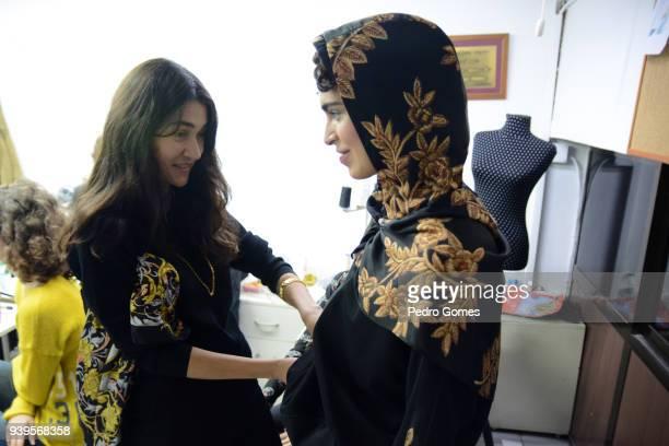Designer Asli Filinta checks the dress of a model backstage ahead of the Asli Filinta show during Mercedes Benz Fashion Week Istanbul at Zorlu Center...