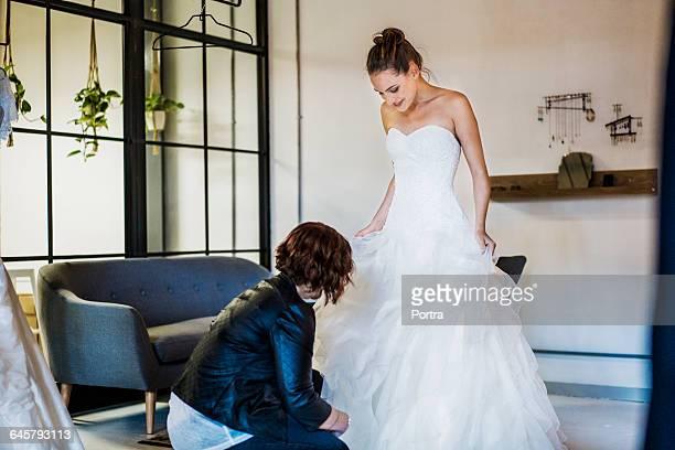 Designer assisting happy bride at bridal shop