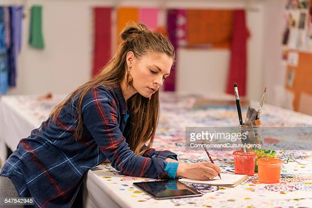 Designer at work table in textile workshop