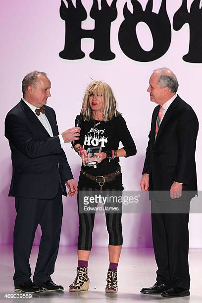 Designer Betsey Johnson receives the Silver Needle Award from the directors of Marist College during the Betsey Johnson Reprise fashion show during...