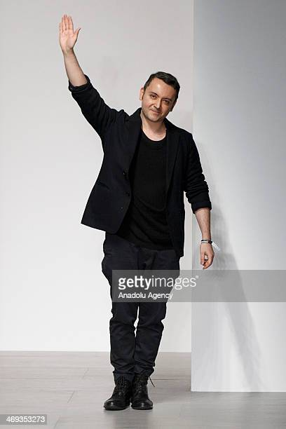 Designer Bora Aksu waves at the audience at the end of his show during the 2014 Autumn / Winter London Fashion Week in London on February 14, 2014....