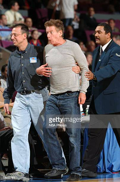 Designer Calvin Klein is assisted by a friend back to their seats with the help of security after approaching Latrell Sprewell of the New York Knicks...