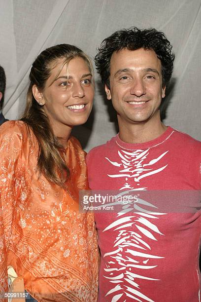 Designer Carlos Miele and Claudine DeMatos pose at a private beach bash party hosted by Brooke Burke and Mount Gay Rum on June 23 2004 at the...