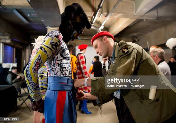 Designer Charles Jeffrey LOVERBOY right gives the last touches to a model's outfit on the backstage during the Autumn/ Winter 2018 London Fashion...