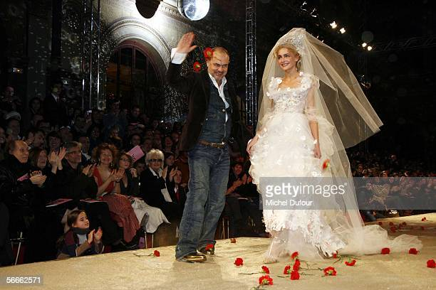 Designer Christian Lacroix appears on the runway with a model displaying a wedding dress during the Christian Lacroix fashion show as part of Paris...