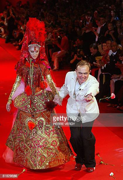 Designer Christian Lacroix throws a flower on the catwalk with a model while acknowledging the audience 09 July 2002 during the autumn/winter...