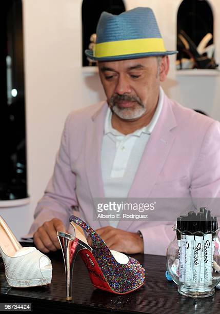 430daa1e575e4 Designer Christian Louboutin signs an autograph at the grand opening of the  new Christian Louboutin boutique