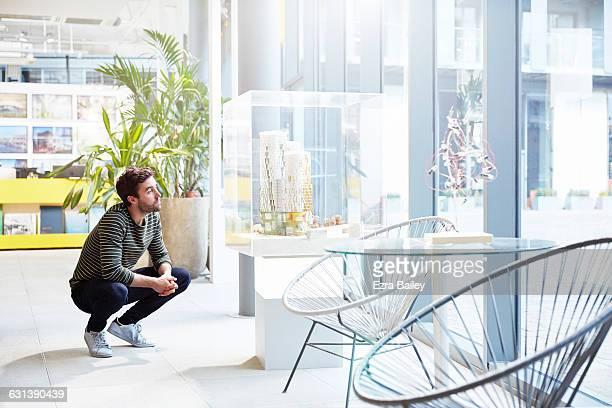 Designer contemplates an architects model.