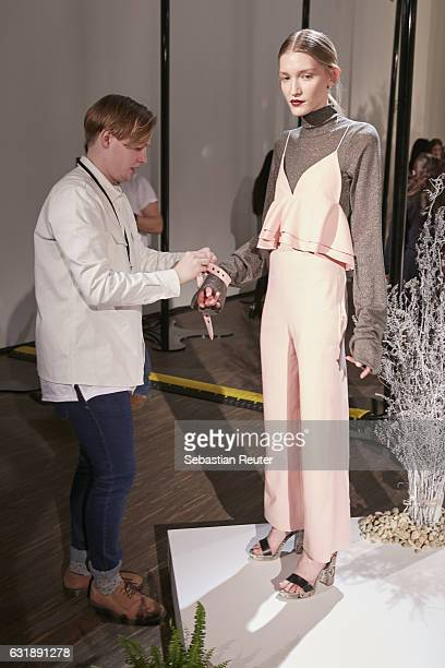 Designer Danny Reinke prepares a model backstage ahead of the Danny Reinke show during the Mercedes-Benz Fashion Week Berlin A/W 2017 at Stage at me...